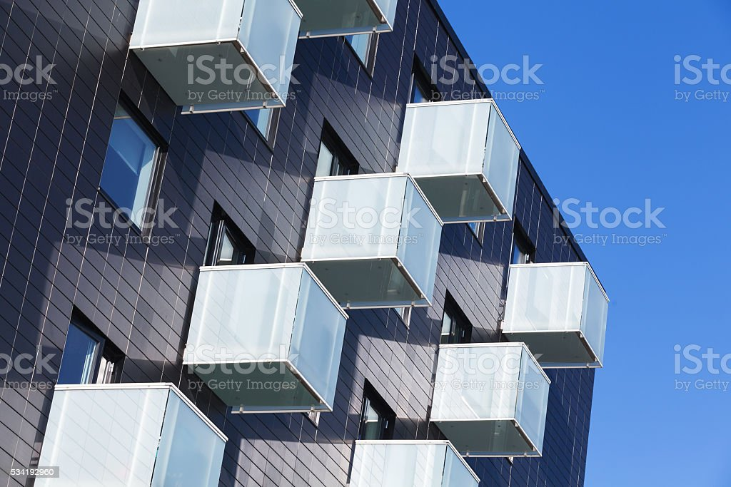 Cube shaped balconies with white glass railings stock photo