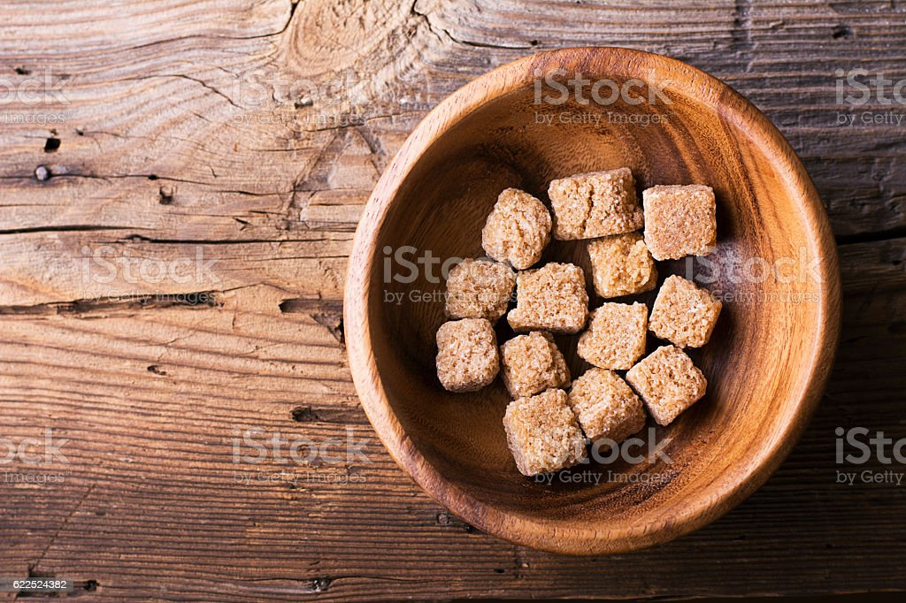 Cubes natural brown cane sugar in a wooden bowl on stock photo