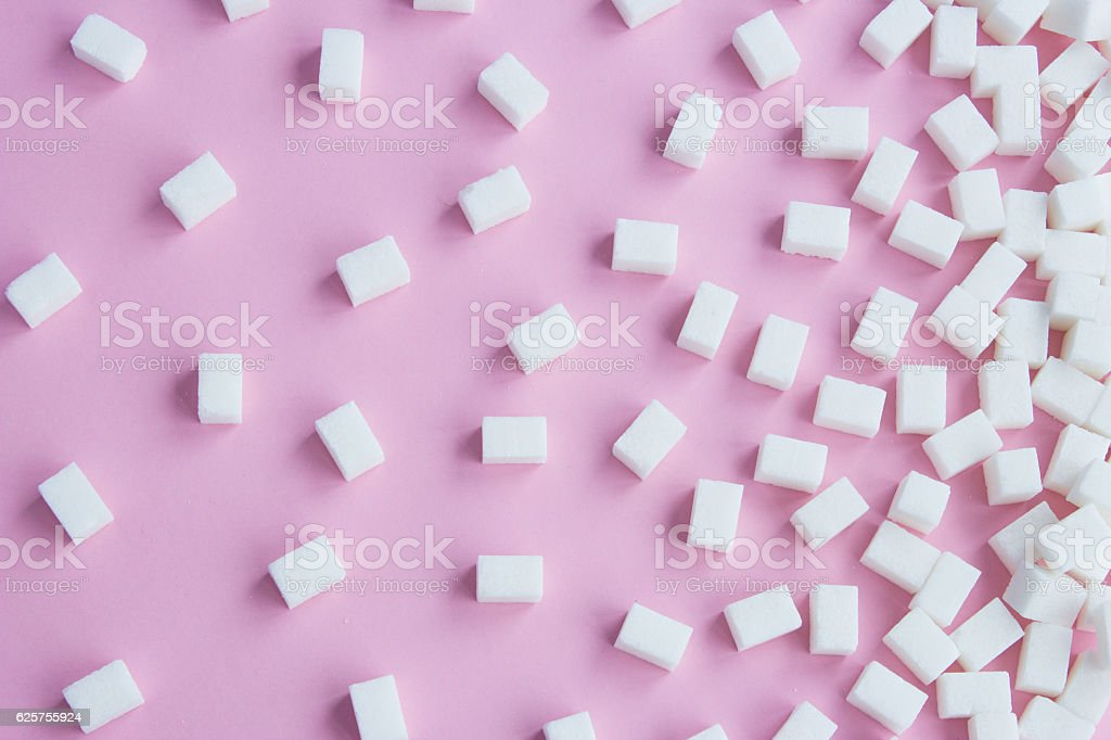 Cubes of sugar on pink background stock photo