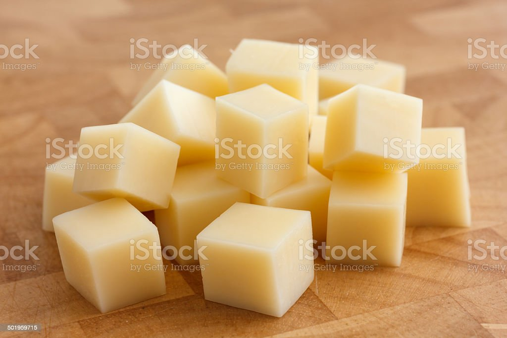 Cubes of yellow cheese stacked randomly on wood chopping board. stock photo
