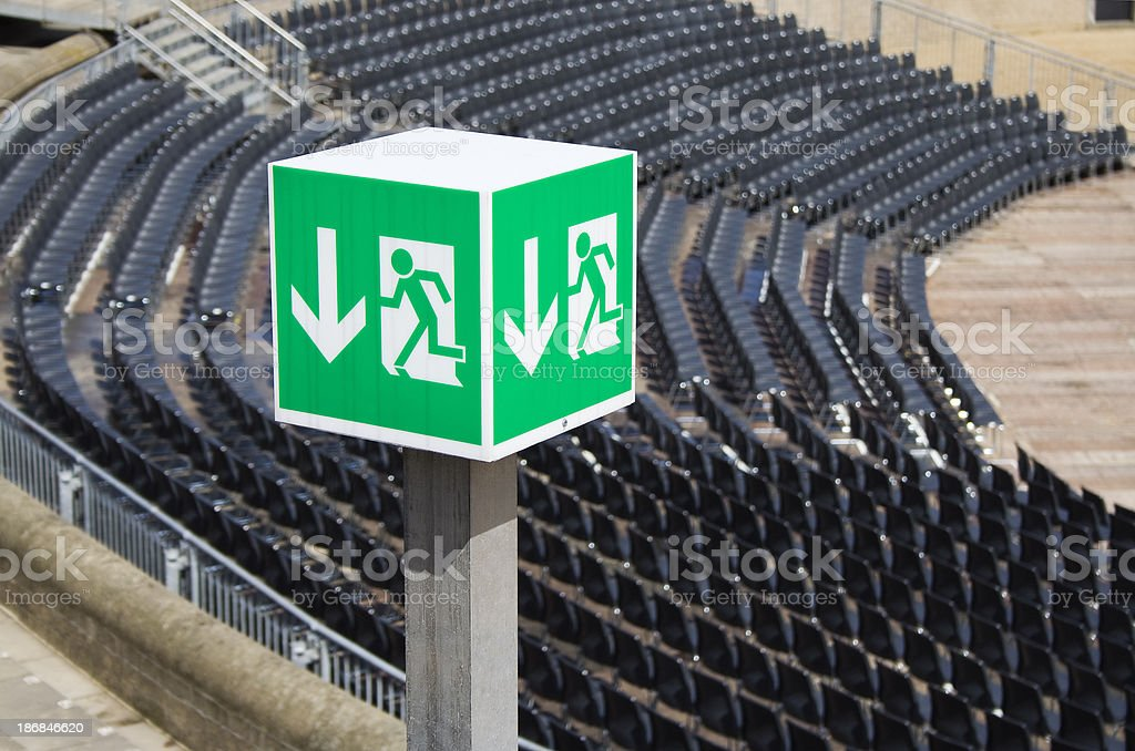 Cubic emergency exit sign and empty stadium stock photo