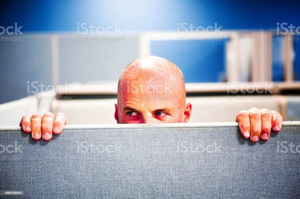 Cubicle worker spying cautiously stock photo