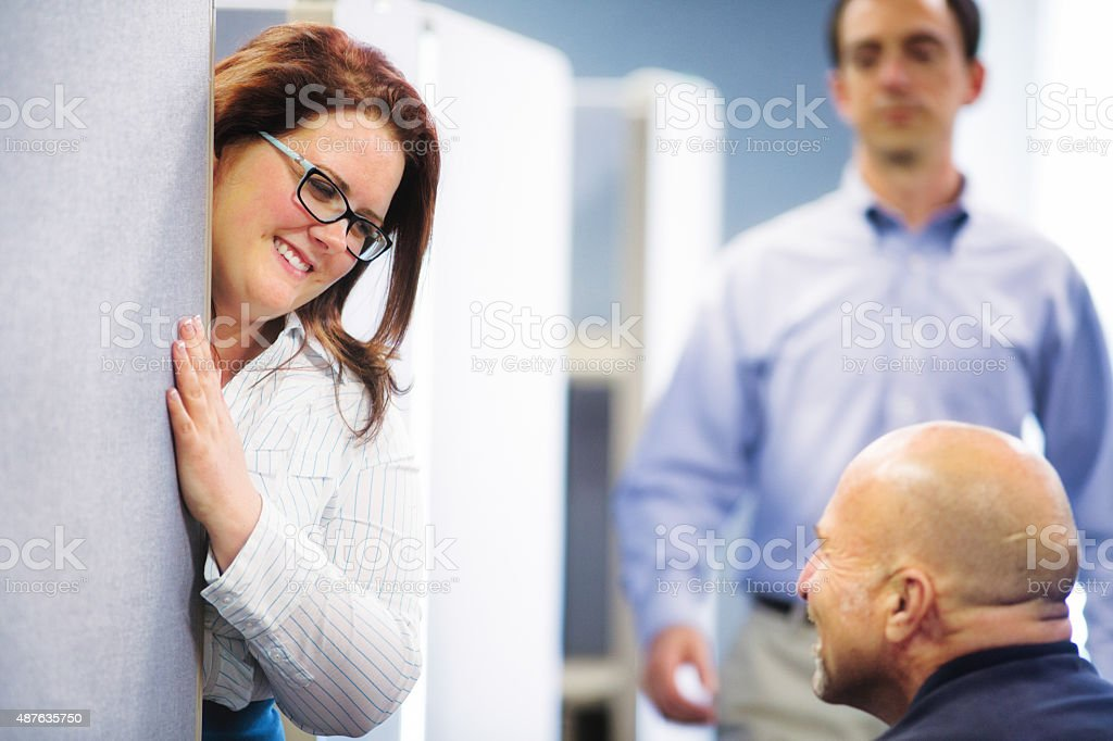Cubicle workers have fun conversation while supervisor is coming stock photo