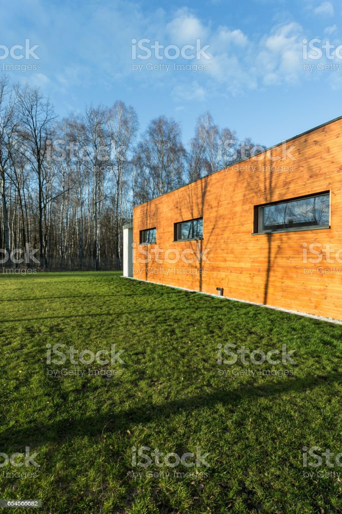 Cuboid wooden house near forest stock photo