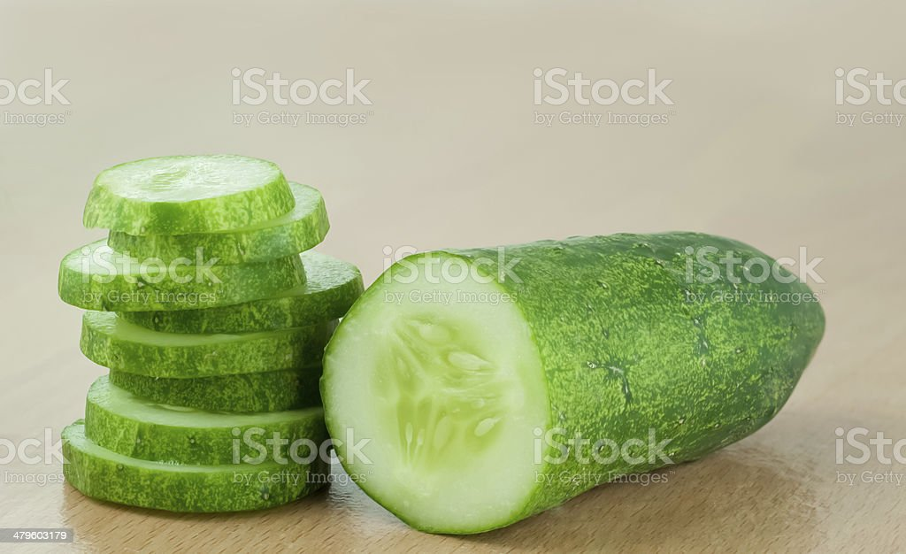 Cucumber half and Slices on wood table background stock photo
