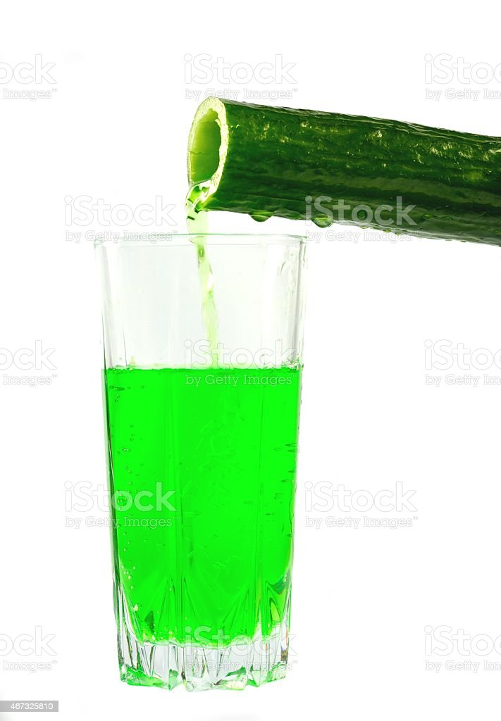 Cucumber juice is poured into a glass stock photo