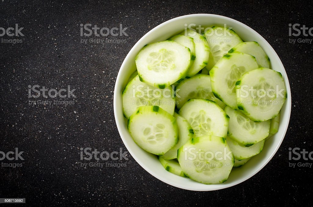 Cucumber slices in white bowl stock photo