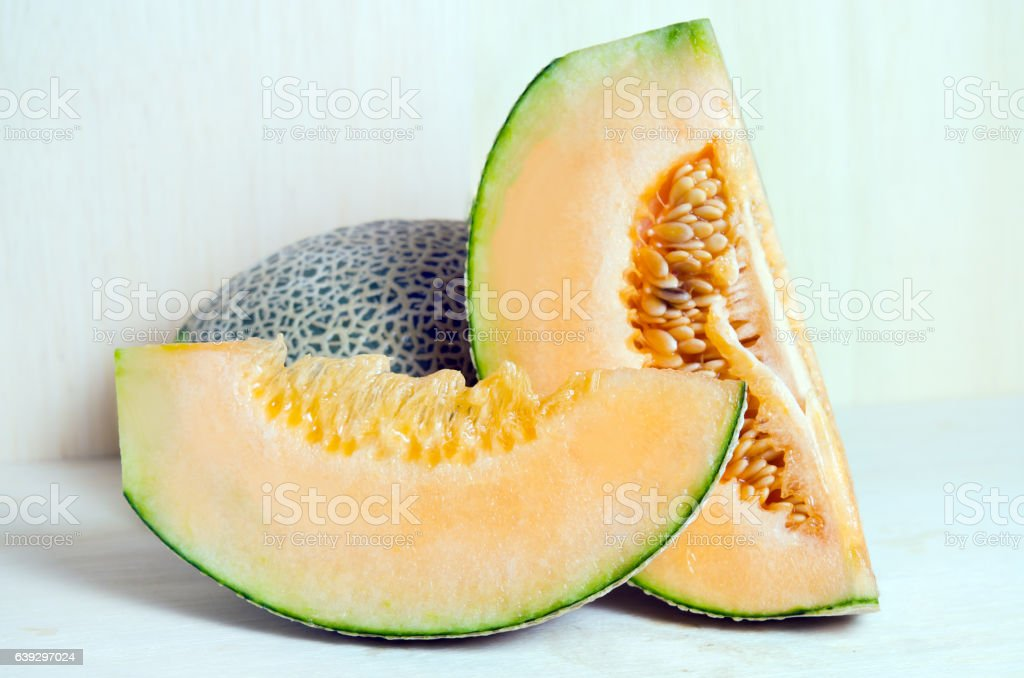 Cucumis melo or melon with half and seeds on wooden stock photo