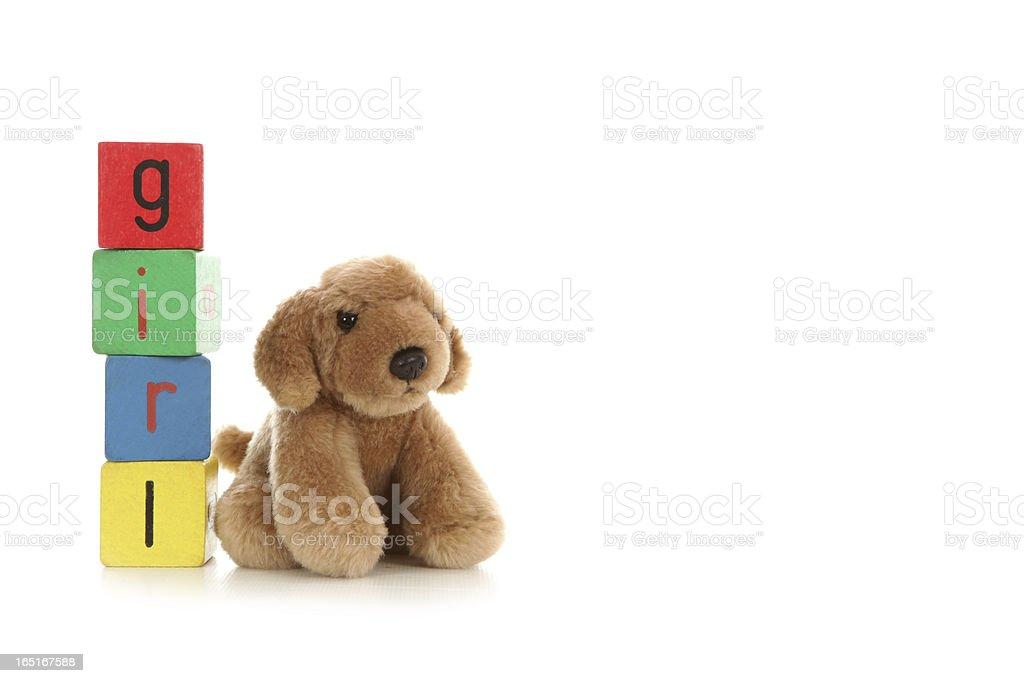 Cuddly toy sat beside alphabet blocks. royalty-free stock photo