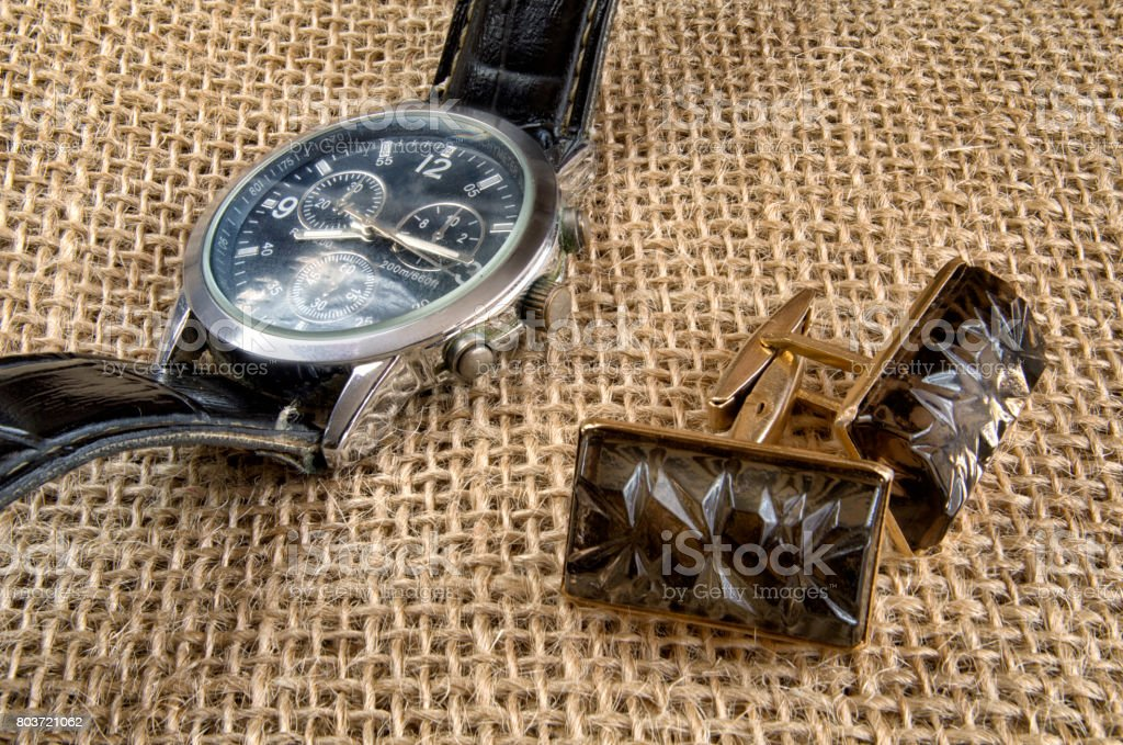 Cuff links and metal watch with the round dial and a black leather thong lie on a sacking. stock photo