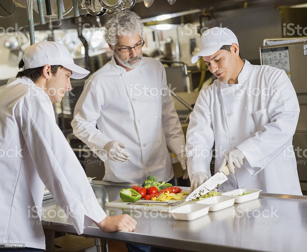 Culinary school intructor teaching students in commercial kitchen stock photo