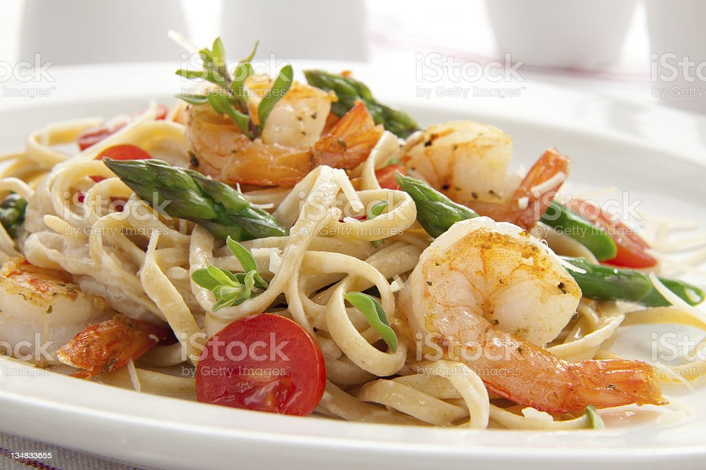 Culinary shot of shrimp pasta with chopped vegetables stock photo