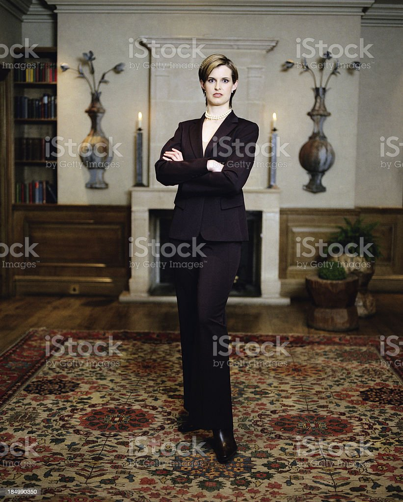 Cultured sophisticated woman standing in the living room stock photo