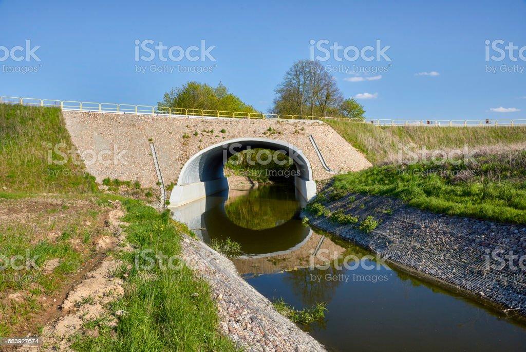Culvert - drain under road for small river. Big pipe under freeway, highway engineering; roadmaking - Poland , Dabrowka Malborska stock photo