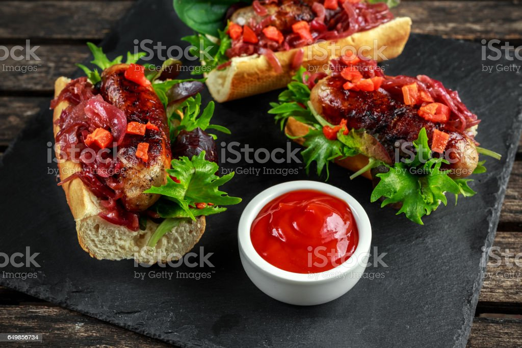 Cumberland sausage hot dogs with caramelized onion, roasted red peppers stock photo