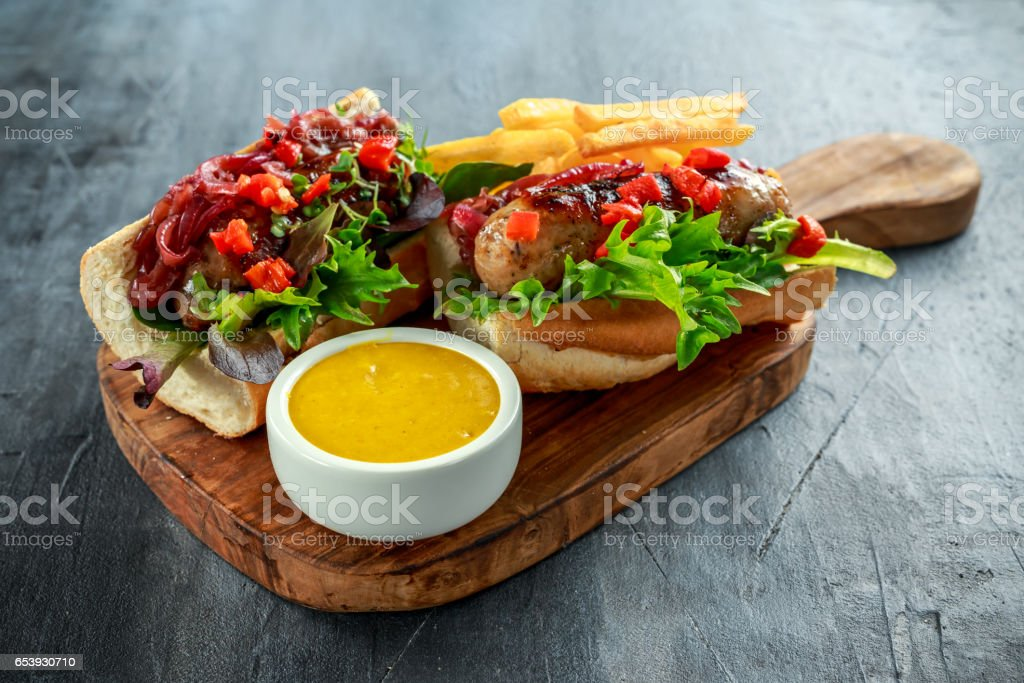 Cumberland sausage hot dogs with caramelized onion, roasted red peppers, french fries. stock photo