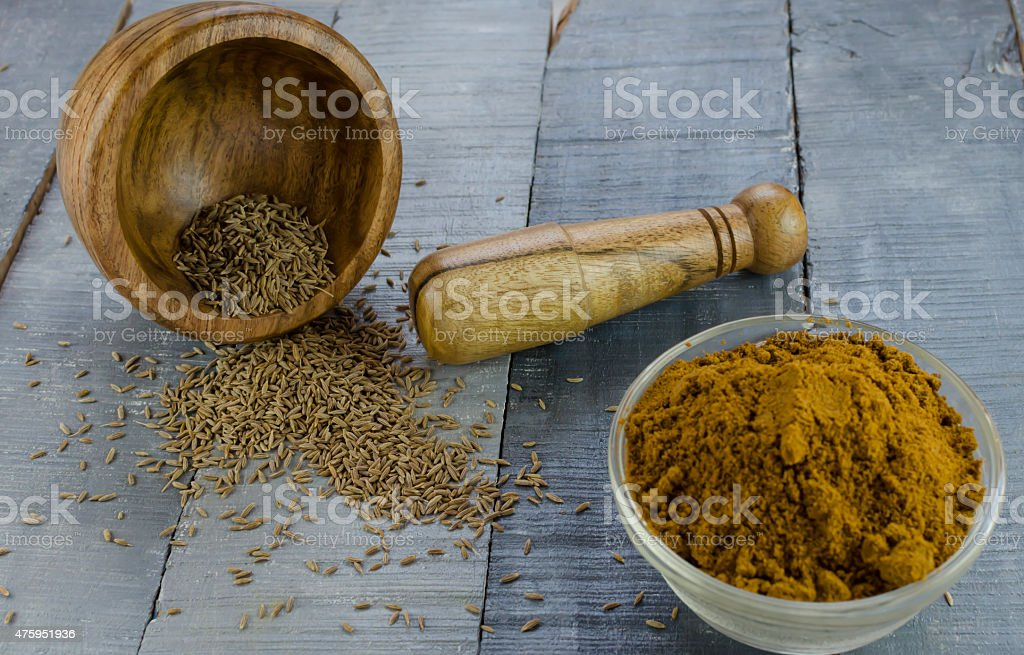 cumin powdered from seeds using mortar and pestle stock photo
