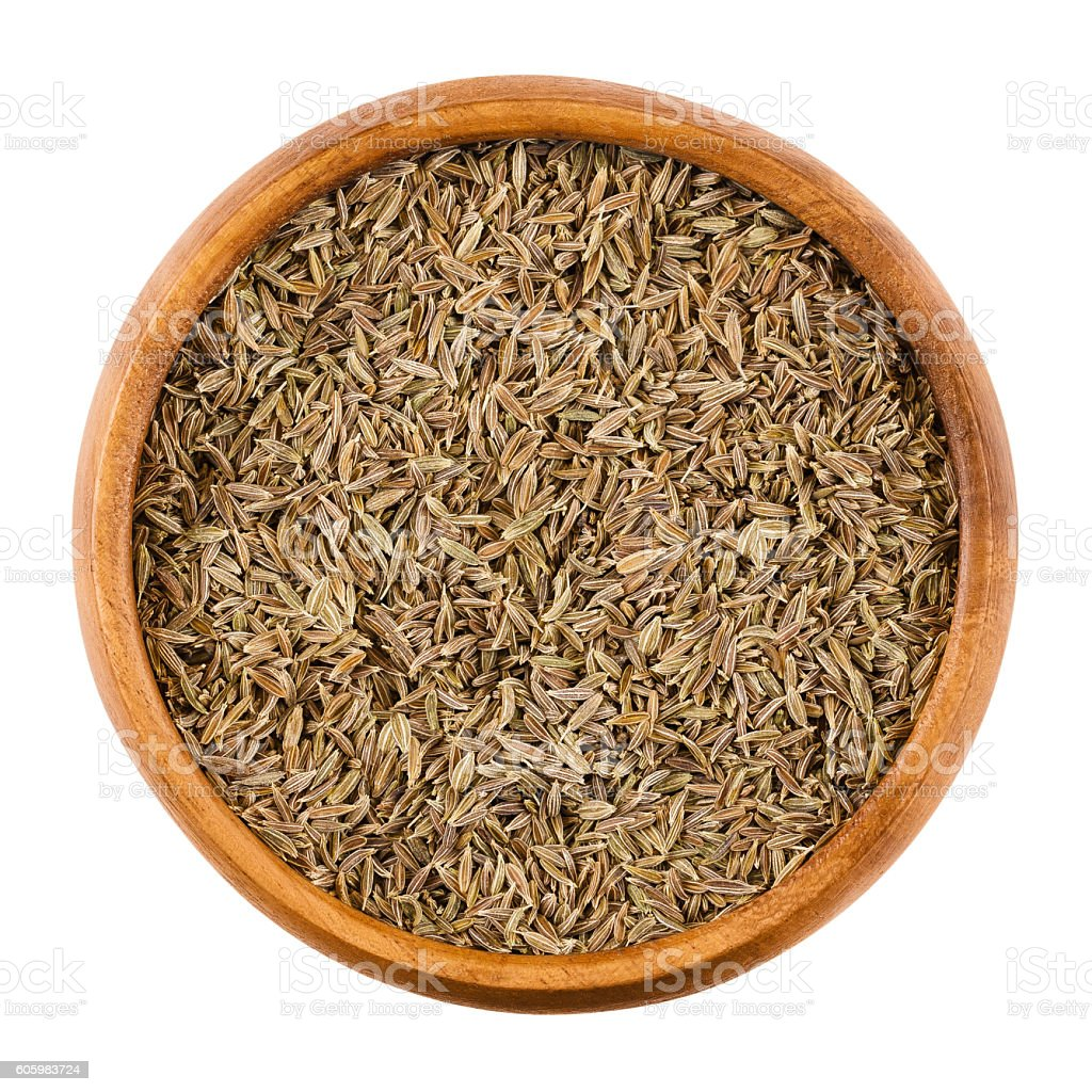 Cumin seeds in a wooden bowl over white stock photo