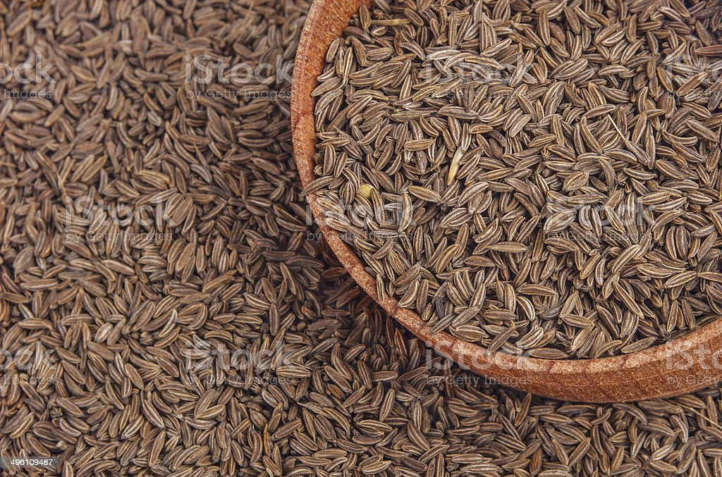 Cumin seeds in a wooden plate stock photo