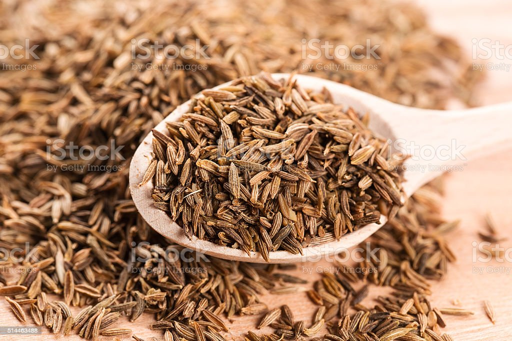 Cumin seeds in wooden spoon stock photo