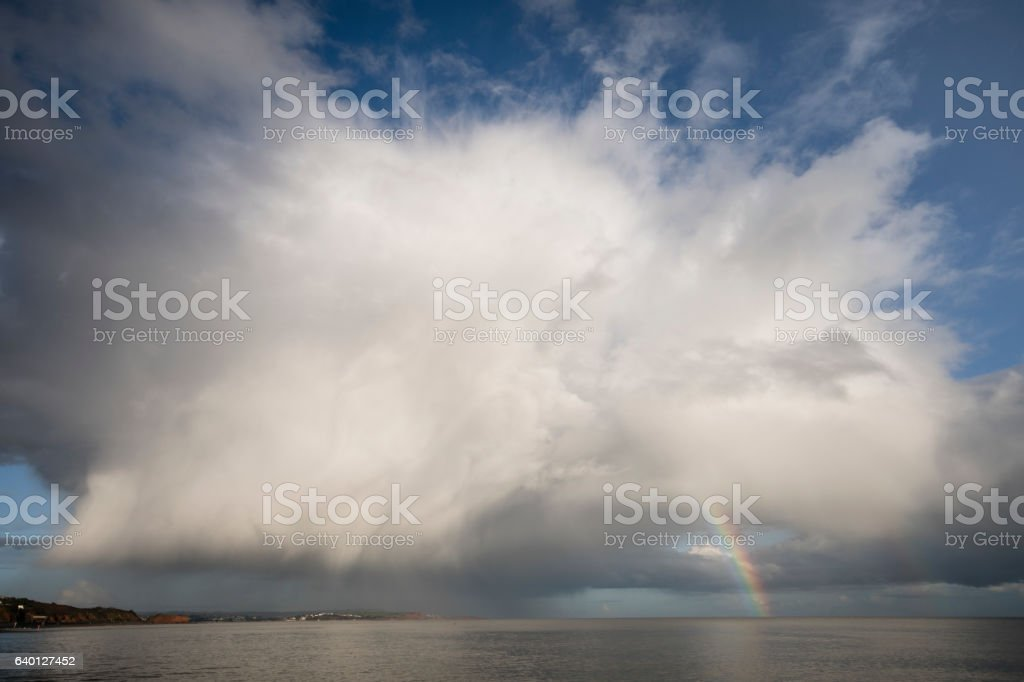 Cumulonimbus cloud with rainbow over Dawlish Warren Devon stock photo