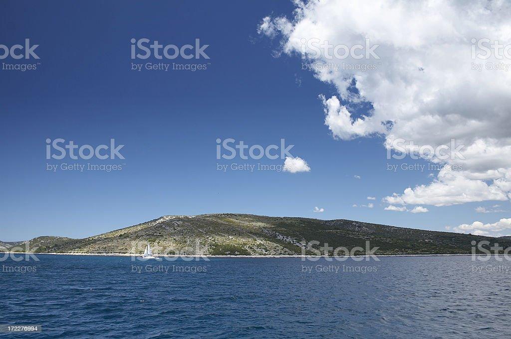 Cumulus clouds over island stock photo