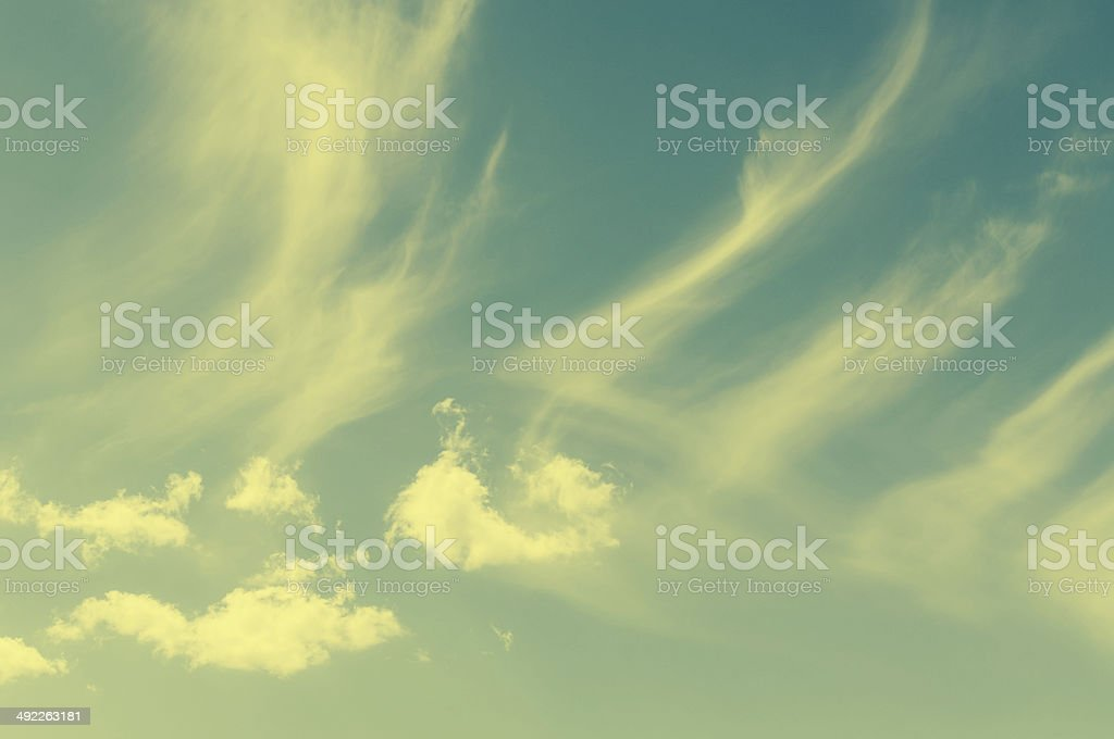 Cumulus with wispy cirrus clouds in retro vintage filter royalty-free stock photo