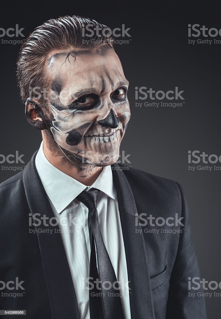 cunning businessman with a makeup of the skeleton stock photo