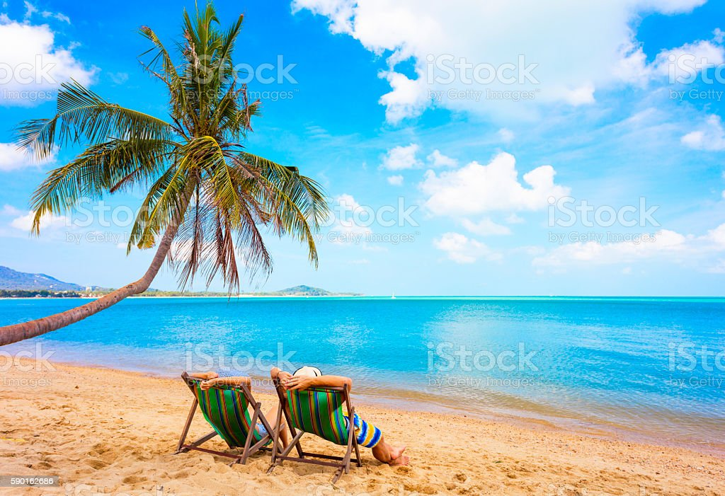 Cuople sitting at beach chair stock photo
