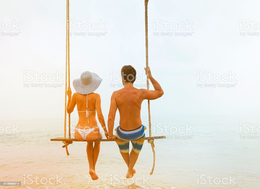 Cuople sitting at rope swings stock photo