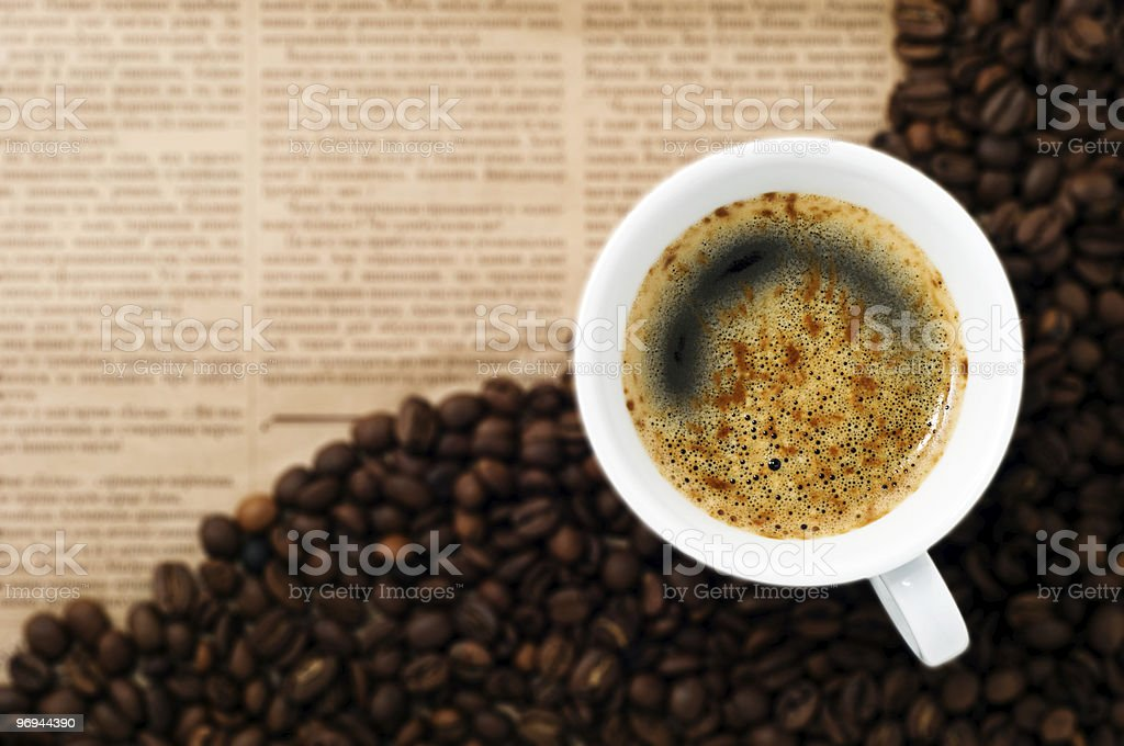 Cup and Coffee Beans on newspaper backgroun royalty-free stock photo