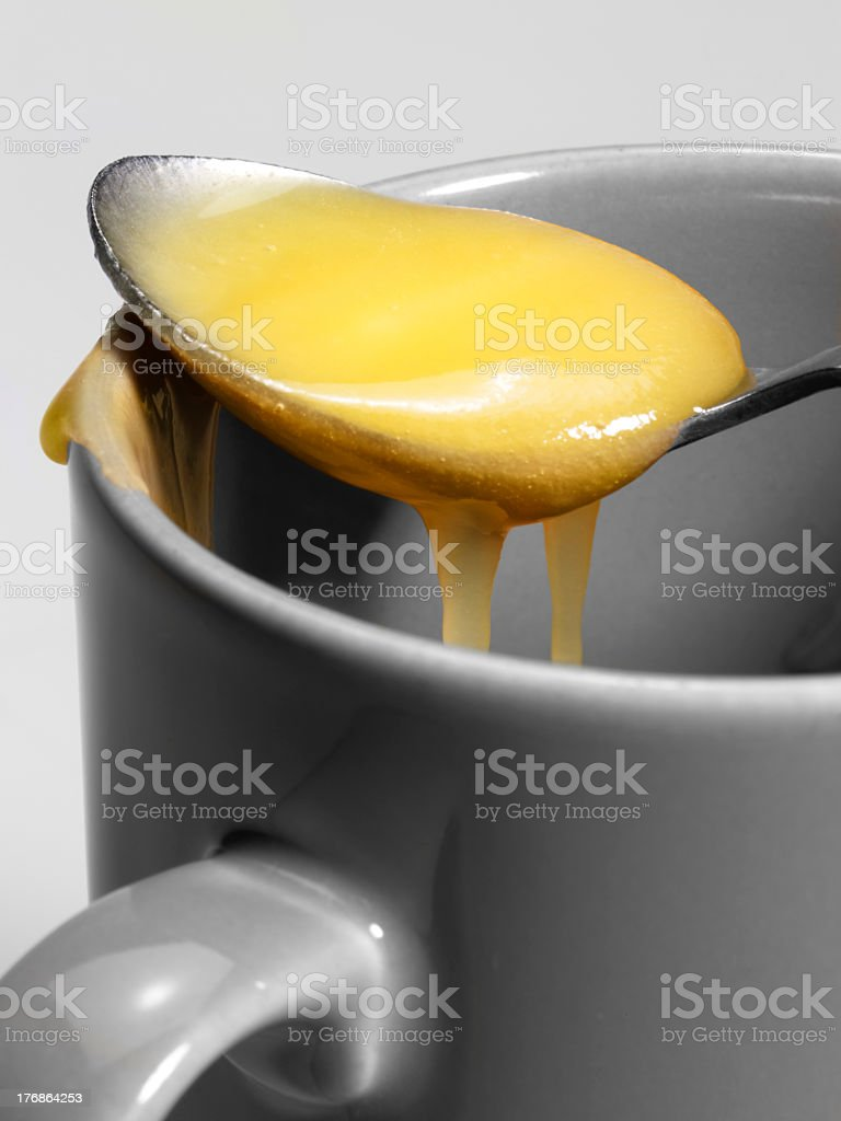 cup and honey spoon stock photo