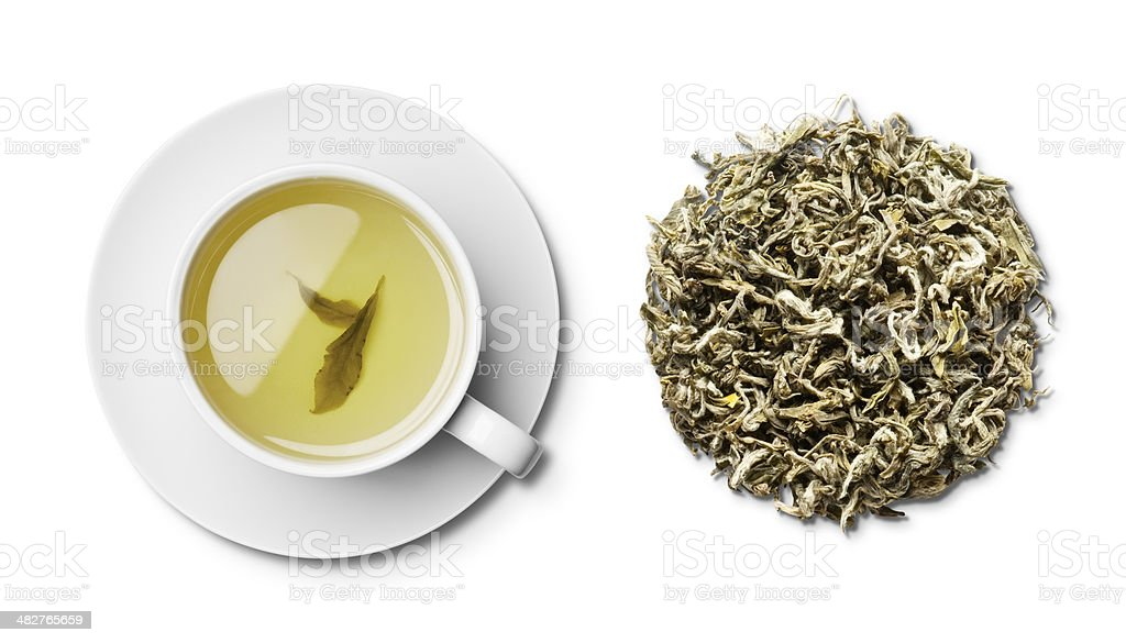 Cup and saucer of green tea and leaves overhead stock photo
