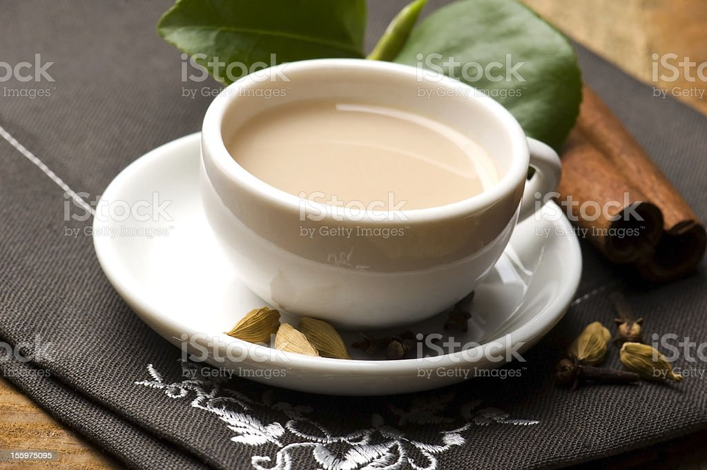 A cup containing masala chai on a saucer royalty-free stock photo