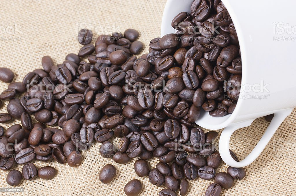 Cup full of coffee beans with sackcloth. royalty-free stock photo