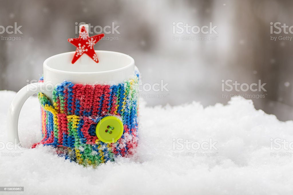 Cup in multi-colored knit cover in snow, outdoors stock photo