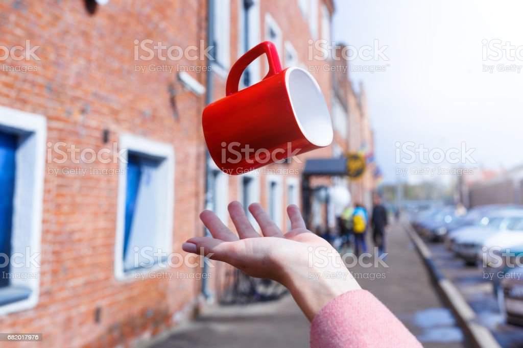 A cup is levitating over the hand in a front of a city background stock photo