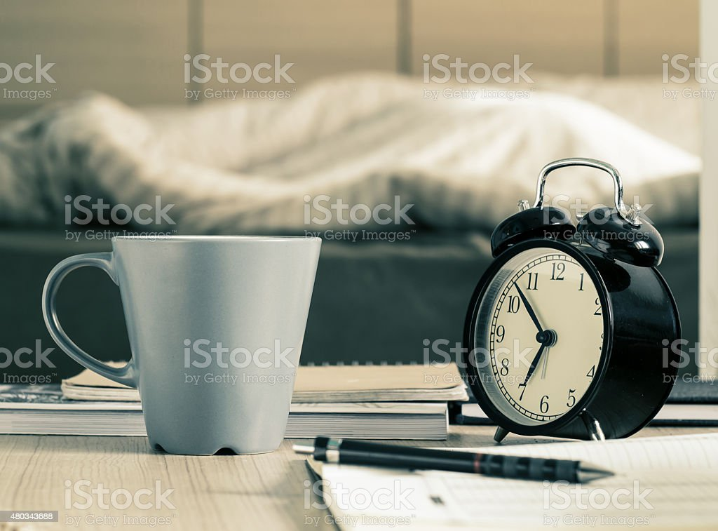 Cup mug and  retro alarm clock on the table stock photo