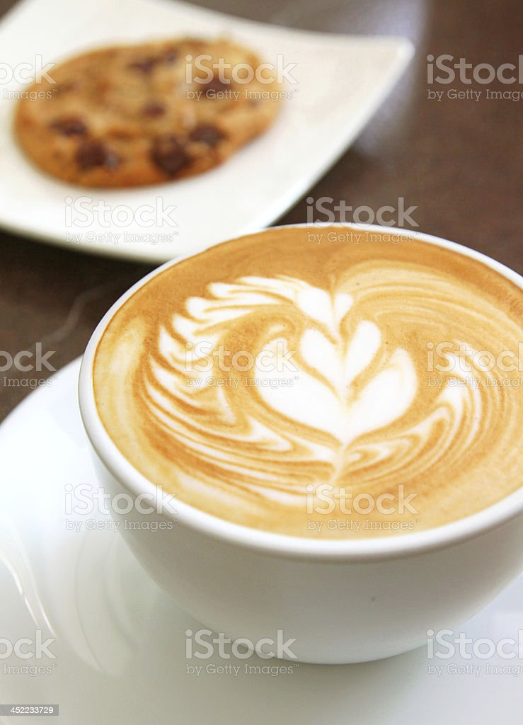 Cup of art latte on a cappuccino coffee with cookie royalty-free stock photo