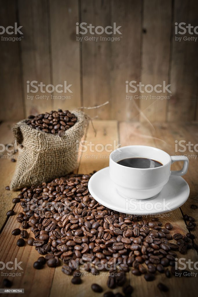 Cup of black coffee and coffee beans on wooden background. stock photo