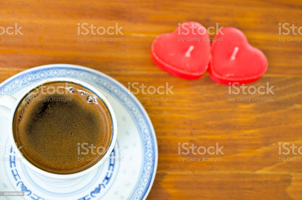 Cup of black coffee and heart shaped candles royalty-free stock photo