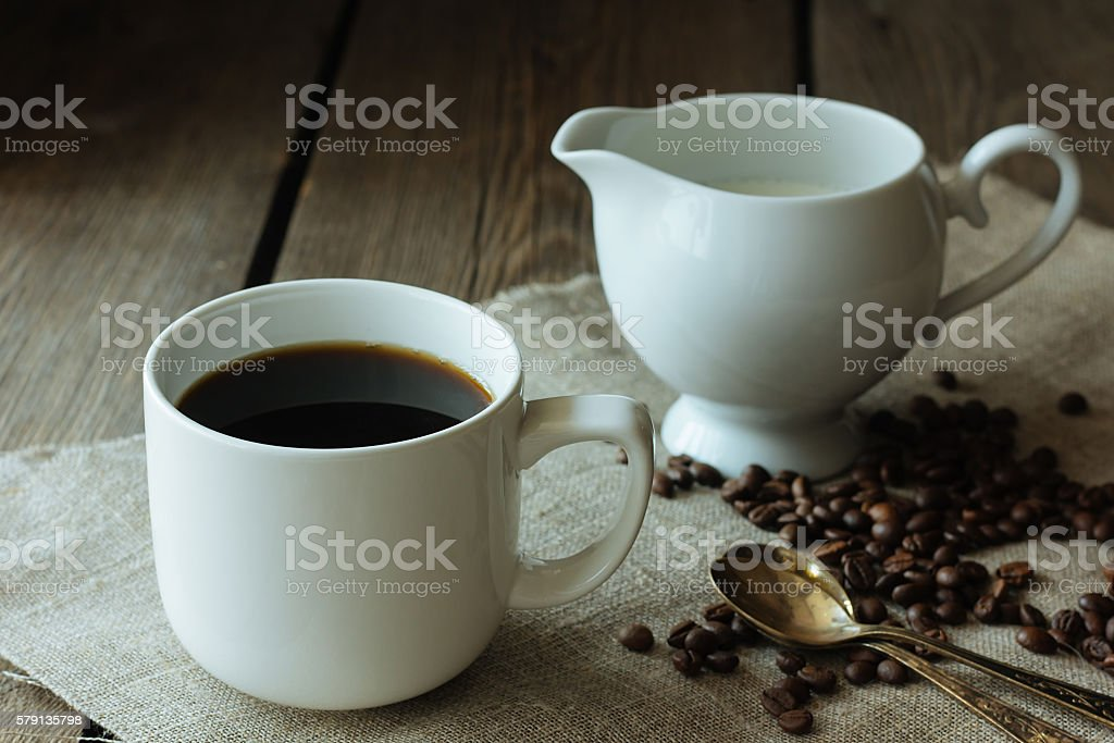 Cup of black coffee and milk jug stock photo