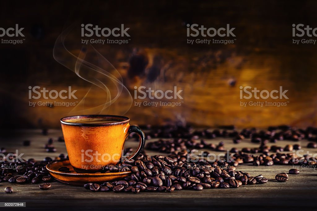 Cup of black coffee and spilled coffee beans. Coffee break stock photo