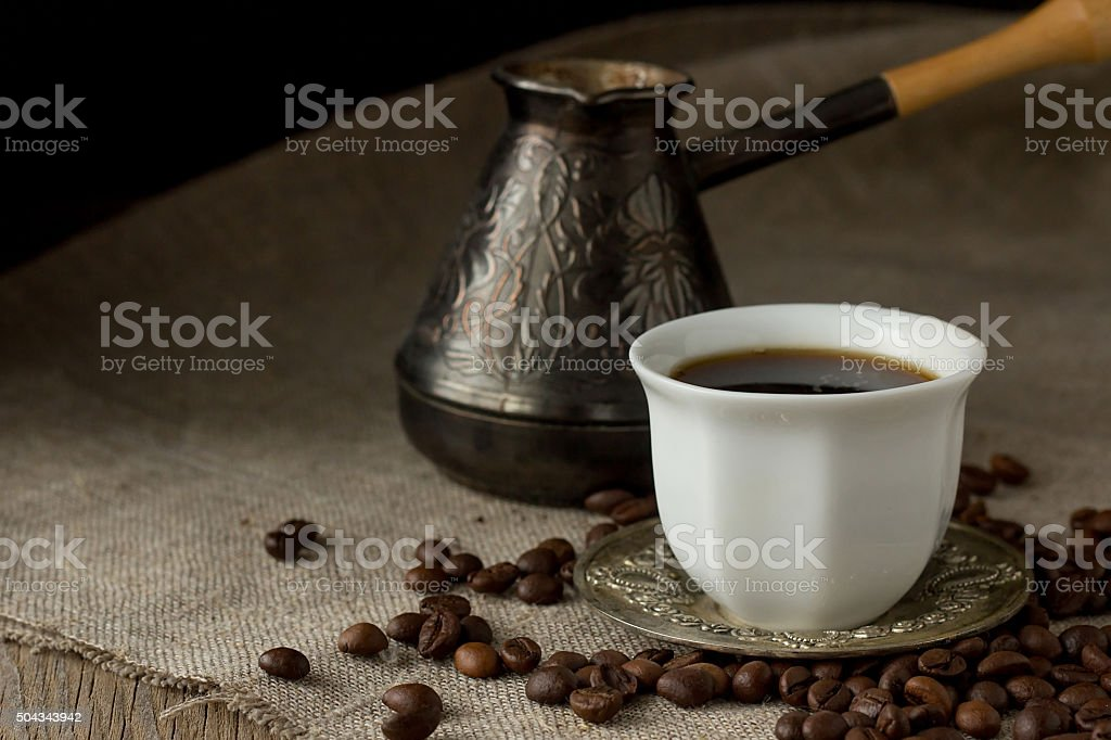 Cup of black coffee, brewing pot and coffee beans stock photo