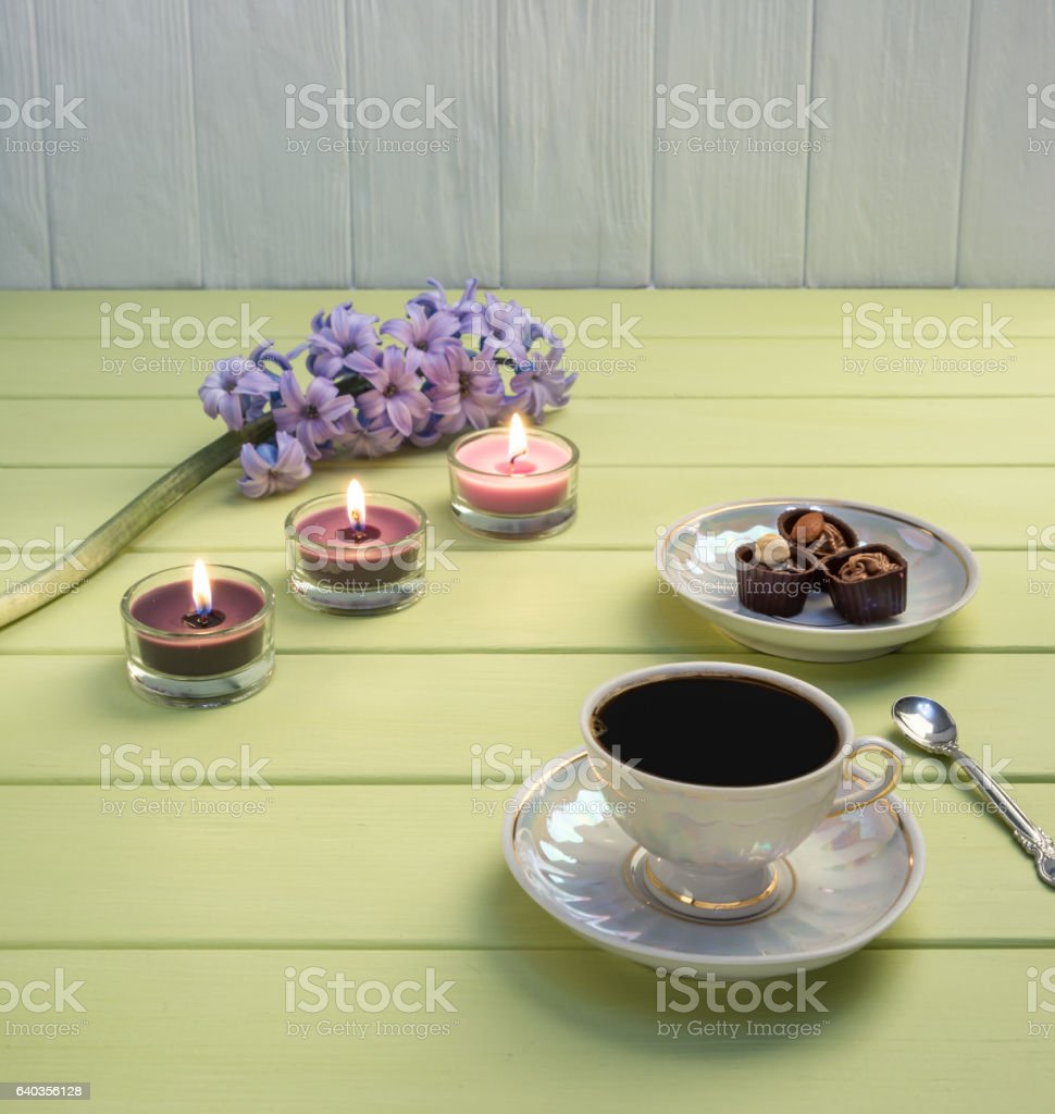 Cup of black coffee, candles and flowers stock photo