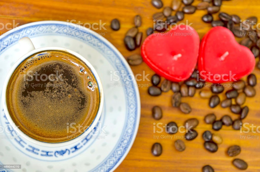 Cup of black coffee, coffee beans and heart shaped candles royalty-free stock photo