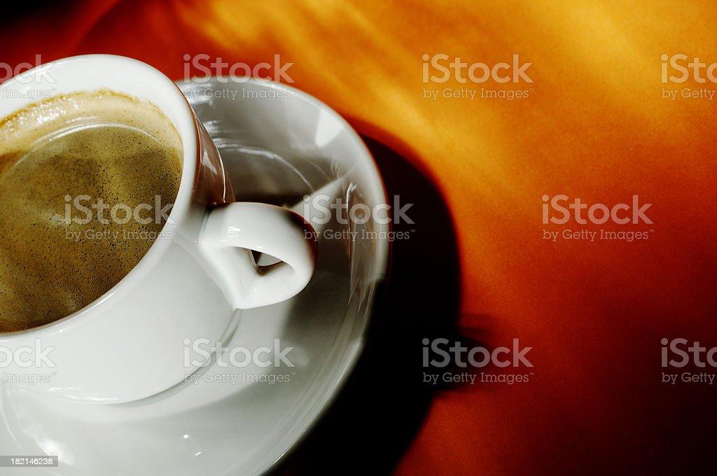 cup of black espresso coffee against vibrant orange royalty-free stock photo