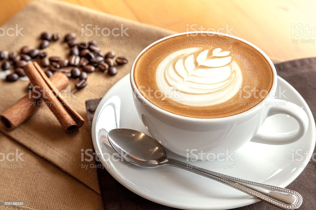 Cup of cafe' latte with coffee beans and cinnamon sticks stock photo