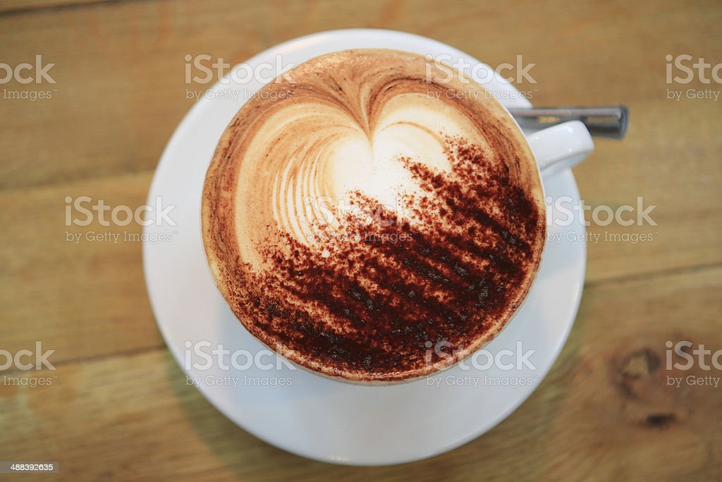 Cup of Cappuccino on a wooden table stock photo