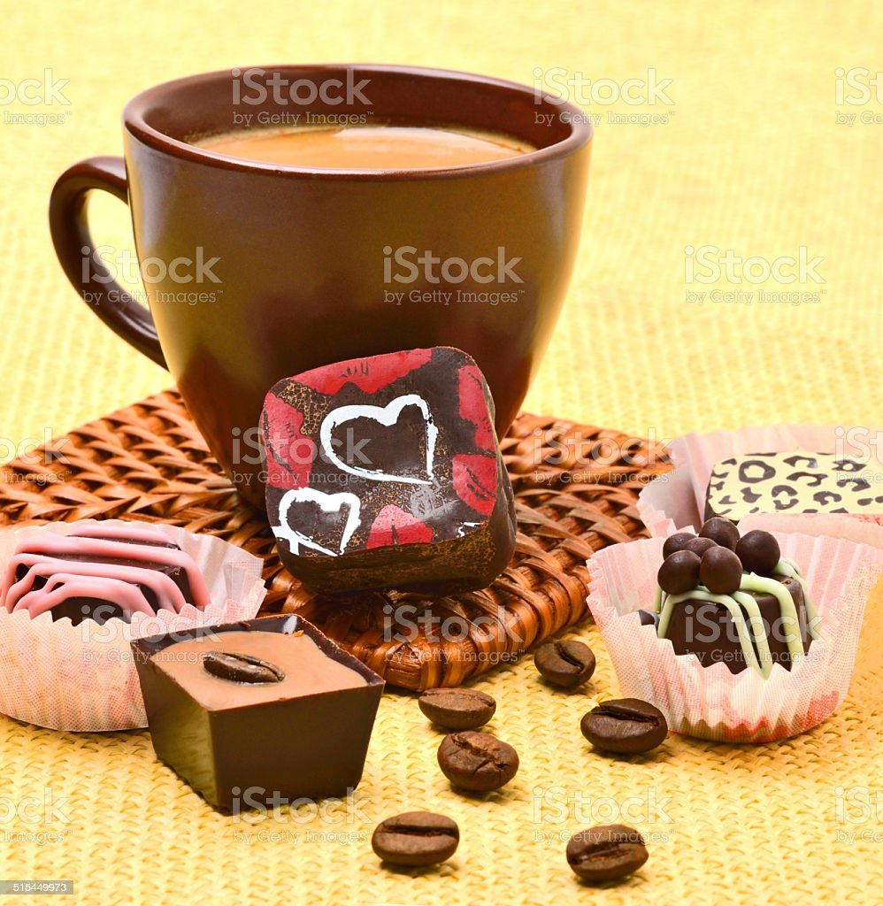 Cup of cappuccino with chocolate sweets and coffee beans stock photo